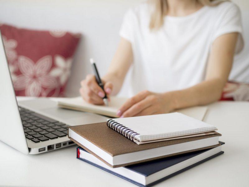 imagen ilustrativa que muestra una persona escribiendo junto a libros y una computadora portatil